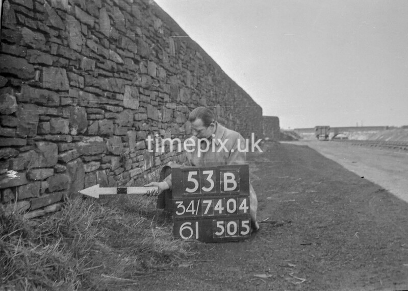 SD740453B, Man marking Ordnance Survey minor control revision point with an arrow in 1940s