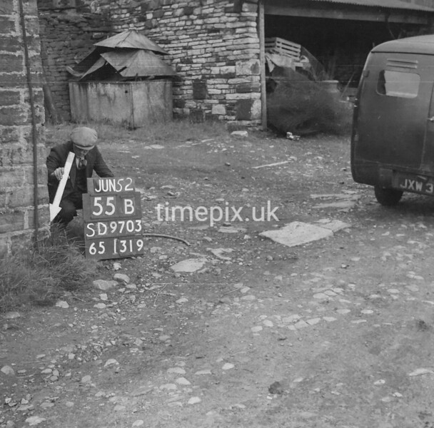 SD970355B, Man marking Ordnance Survey minor control revision point with an arrow in 1950s