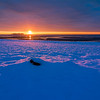 Sunrise over Charles Island casting beautiful light on freshly fallen snow on the beach at Silver Sands State Park in Milford, Connecticut, USA.