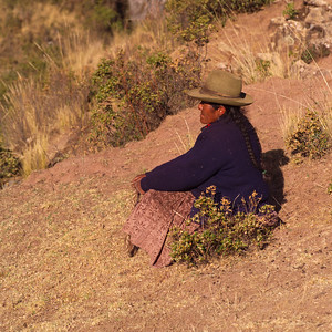 Peruvian woman sitting on a hillside