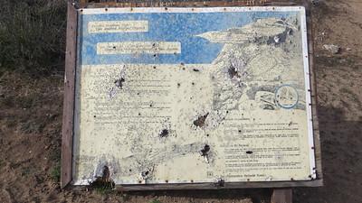 Trailhead sign full of bullet holes.