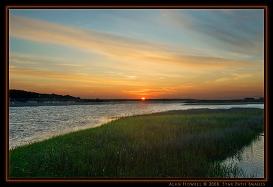 The first rays of a warm and breezy sunrise over the inlet at Ocean Isle Beach...looking over towards Emerald Isle.