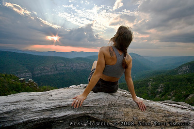 Soaking up the last rays of the day, a hiker enjoys the sunset as seen at the Chimneys area of Table Rock and Linville Gorge.