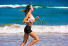 Brunette girl running on the beach headphones