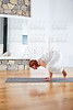 Yoga Crow Pose in wooden floor gym