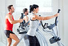 man and woman with elliptical cross trainer at gym