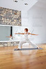 Yoga Warrior two II pose in wooden floor