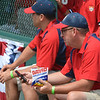 Head coach Lou Fresta eats some DAVID sunflower seeds while sending a text or a tweet on his phone prior to the Rebels game against Sherman Oaks at the Cooperstown Park.