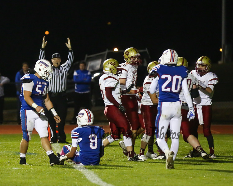 Winnacunnet's #8 Liam Viviano sits on the goal line while Clipper players surround and congratulate #80 Justin Lent after making a catch off a deflected ball during Friday Night's Football game between Winnacunnet and Portsmouth High Schools on 10-16-2015 @ WHS.  Matt Parker Photos