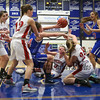 Winnacunnet's #14 Meg Knollmeyer tips the ball to #23 Kaya Cadagan as she jumps on a loose ball with Pinkerton's #24 Sara McLeman and #3 Jamie Caron during Monday's Div I Semi-finals Playoff Girls Basketball game between Winnacunent and Pinkerton Academy @ SNHU on 3-9-2015.  Matt Parker Photos