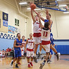 Winnacunnet's #21 Logan Keene gets fouled by Spaulding's #5 Arie Breakfield and #13 Isiah Rose as he drives in for a layup during Wednesday's Championship game at the  2016 Oyster River High School Bobcat Invitational Boys Basketball Tournament on 12-28-2016 @ Oyster River HS.  Matt Parker Photos