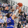 UNH's #5 Daniel Dion takes a jump shot from outside the 3 point line with UML defender #22 Matt Harris getting a hand up during Wednesday's America East Basketball game between UNH and UMass Lowell on 1-25-2017 @ Lundholm Gymnasium, UNH, Durham.  Matt Parker Photos