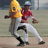 Roslyn's Jordan Garnick ignores Fort Washington runner Dan Brown as he concentrates on fielding a grounder to make the force at first to end the inning.<br /> Bob Raines 7/11/11