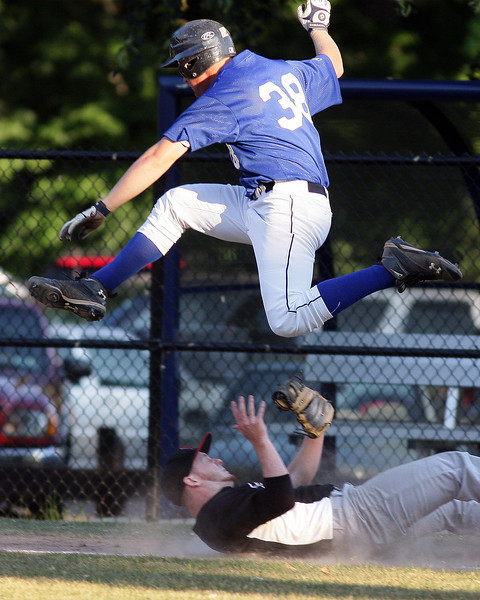 Glenside's Jon Gyles hurdles Northeast's pitcherJohn Trasser on his way to first.<br /> Bob Raines 6/29/11