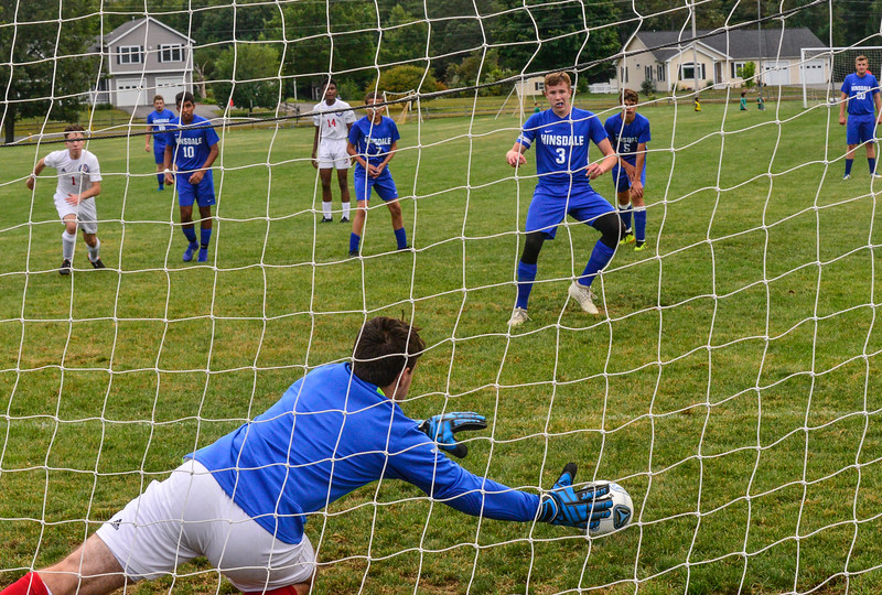 KRISTOPHER RADDER — BRATTLEBORO REFORMER<br /> Hinsdale's Alex Gaffney makes a goal on a free kick as Mount Royal's Tristian Oveletle couldn't reach the ball during a boys' soccer match at Hinsdale Middle High School on Thursday, Sept. 12, 2019.