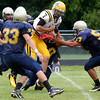 Lower Moreland defenders pull down McDevitt quarterback Christian Conner running a keeper.<br /> Montgomery Media staff photo by Bob Raines<br /> 9/2/11