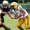 McDevitt's Keith Young looks for a hole as Lower Moreland's Joe Kehoe bores in to make the tackle..<br /> Montgomery Media staff photo by Bob Raines<br /> 9/2/11
