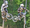 Pro BMX Racers Ty Robinson and Raymond Yoder cross it up over a tabletop jump.