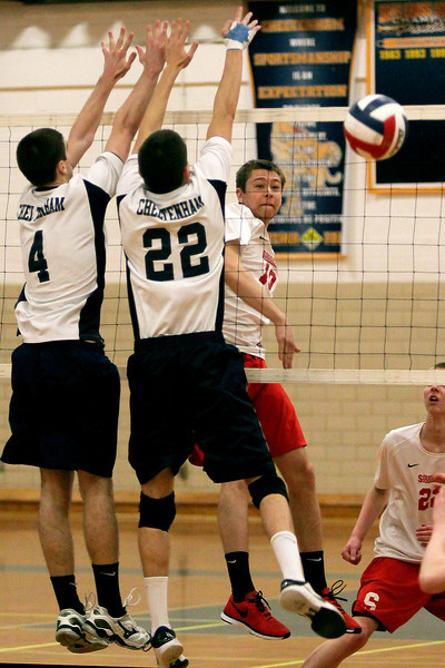 Souderton's Vince Kowalick spikes the ball past Cheltenham's Brett Mayne and Ben Doyle.