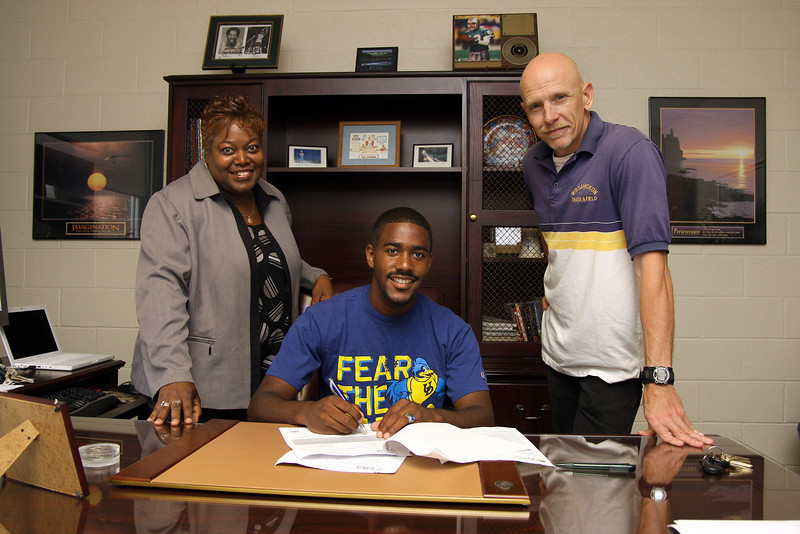 Tyreece Clayton signs a letter of intent to run track at University of Delaware. With him are his mother Vanetta Clayton and Coach Don Betterly.<br /> Bob Raines 6/10/10