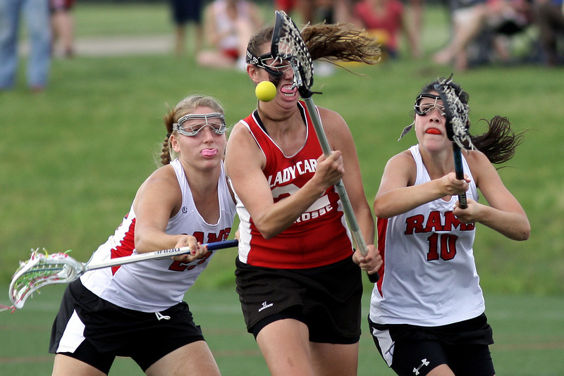 Upper Dublin's Kelly Cross loses the ball as she is checked by  Harriton's Megan Rubenstein, right, and Hilary Lemonick.<br /> Bob Raines 5/24/11