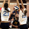 St Basil's Olivia Carter spikes the balll between Villa Maria's Danielle Hillman, left, and Kaleigh Oates.