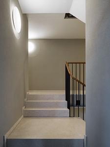 16 Haus A: Im Treppenhaus liegen die versetzt angeordneten Standardleuchten auf einem glatten, runden Wandspiegel. | House A: the irregularly placed standard lights in the stairwells are mounted on a smooth, round wall mirror.