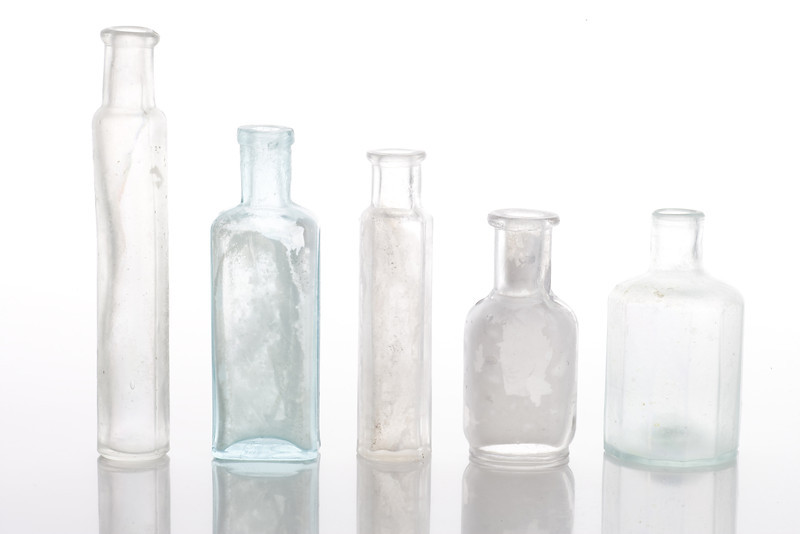 Antique bottles on pure white table with reflections and isolated background