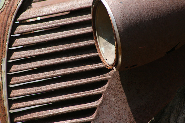 Grill and light detail of very rusty antique car.