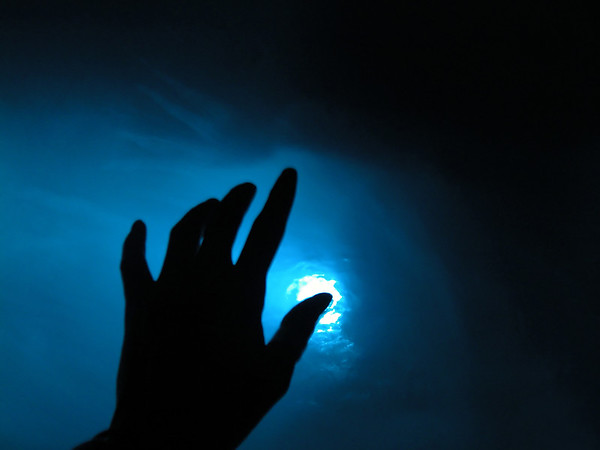 Hand reaching into blue light.
