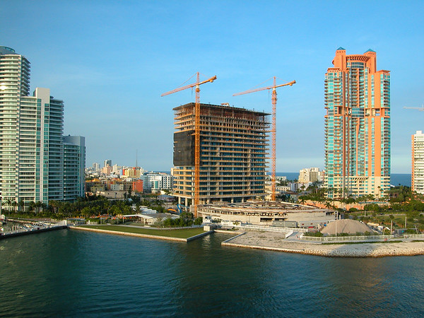 Florida Coast real estate development. Cranes flank the work-site while other high-rise buildings stand tall nearby.