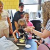 Family members take turns Friday looking at a butterfly egg on a leaf during the showcase. JENN SMITH - THE BERKSHIRE EAGLE