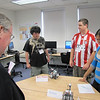 MassBay President John O'Donnell reviews the robotics projects presented by (From left) Nick Dieher, 19, of Natick; Ben Cartier, 18, of Natick; and Neha Jain, 19, of Westborough as part of MassBay's Summer Bridge program