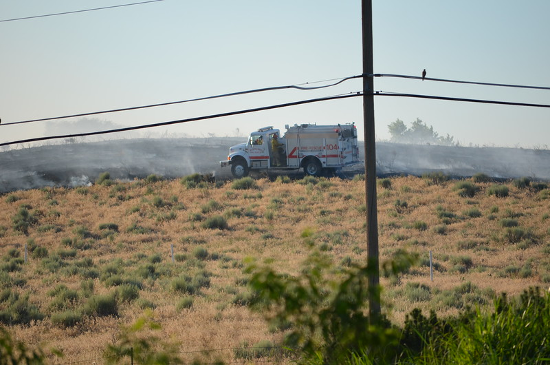 A Sterling Fire truck fights a grass fire in Country Club Hills Tuesday evening, as seen from Juniper Drive looking northwest. (Lisa Young/Journal-Advocate)