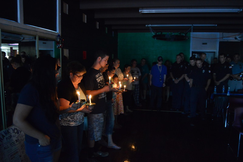 Volunteers hold lit candles in memory of the eight police officers killed in Dallas and Baton Rouge this month during Sterling United's community appreciation event Thursday night at Two Roses.