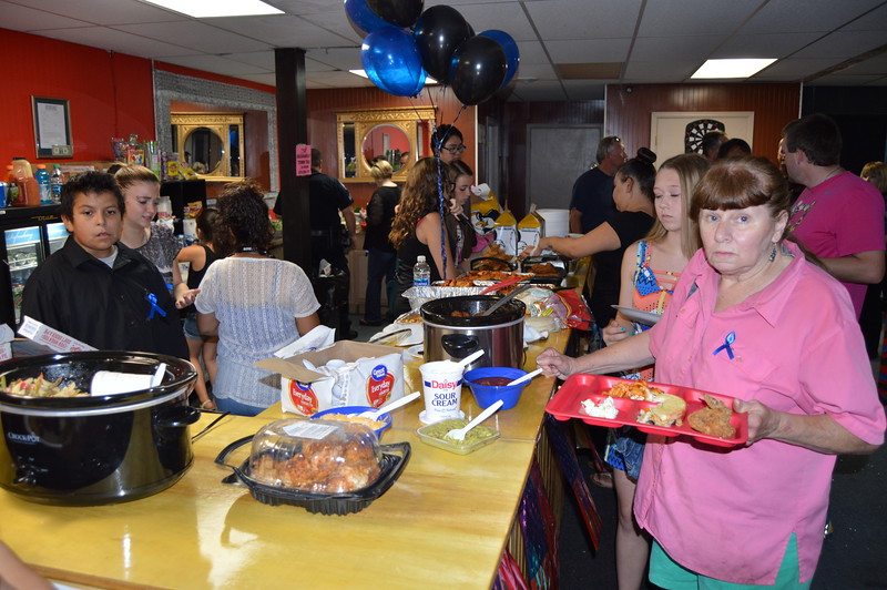 Community members fill their plates from a large variety of foods at the potluck dinner.