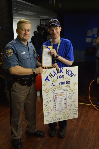"Michael Walker, right, the Sterling resident who came up with the idea for an appreciation event for local law enforcement, presents a poster board signed by supportive community members and a ""law enforcement survival kit"" to Capt. Gaylon Grippin of the Colorado State Patrol."