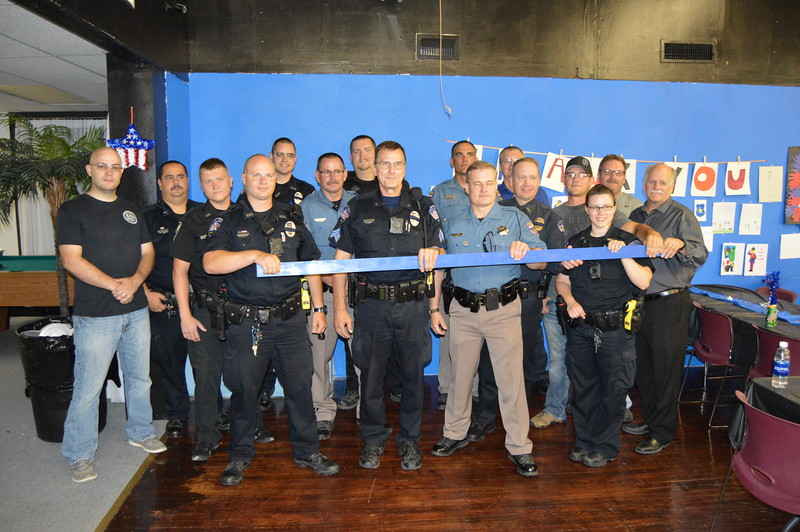 "Officials from various local law enforcement agencies hold ""the blue line"" for a photo at Sterling United's community appreciation event Thursday, July 21, 2016 at Two Roses in Sterling, Colo."