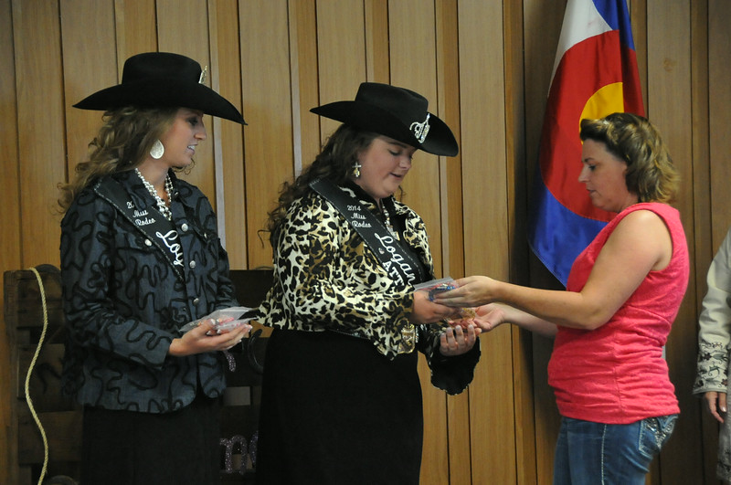 Deb Bates of InnerBeautyOut Designs presents jewelry sets to Miss Rodeo Logan County Regan Wheeler, left, and MRLC Attendant Bobbi Jo Lingreen during the MRLC contest Saturday, Aug. 2, 2014.