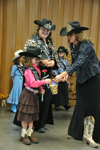 MRLC Regan Wheeler, right, and Attendant Bobbi Jo Lingreen present Little Miss Ayla Baney with gifts during the 2014 Logan County Royalty Contest Saturday, Aug. 2, 2014..