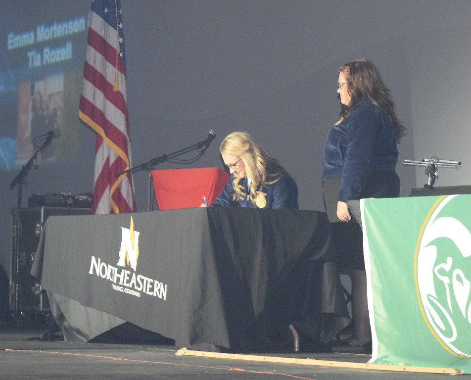 Tia Rozell looks on as Emma Mortensen signs her letter of intent to play basketball for Northeastern Junior College during the opening session of the 88th Annual Colorado FFA State Convention Tuesday, June 7, 2016.