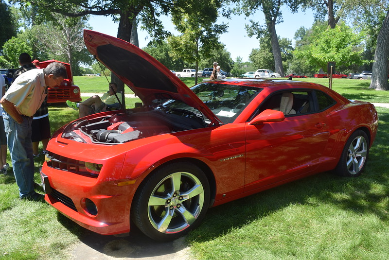 A visitor looks over a 2010 Chevrolet Camaro SS, owned by Eric Hernandez, of Sterling, was among the vehicles on display at Colorado Flatlanders 25th Annual Rod Run in the Park Saturday, July 9, 2016, at Pioneer Park.