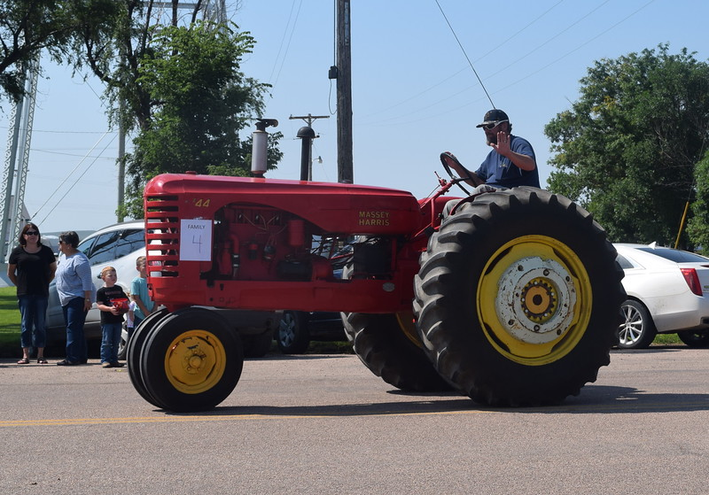 Mike Foster waves as he drives a tractor from Devie Classic Tractors through downtown Crook during the Crook Fair Parade Saturday, July 29, 2016.