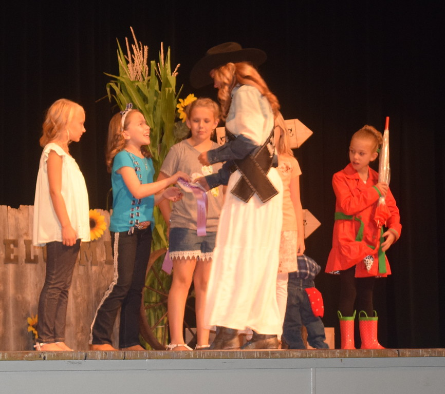 """Queen Contestant McKaylin Schreiner congratulates Ayla Baney reserve champion in the junior division of the """"Equines, Bovines and Little Buckaroos!"""" Logan County Fair 4-H Fashion Revue Friday, July 29, 2016."""