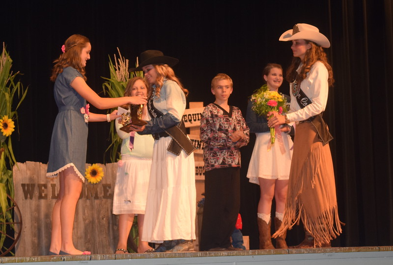 "Queen Contestant McKaylin Schreiner and Miss Rodeo Logan County 2016 Abbey Brower present awards to Lauren Fritzler champion in the intermediate division of the ""Equines, Bovines and Little Buckaroos!"" Logan County Fair 4-H Fashion Revue Friday, July 29, 2016."
