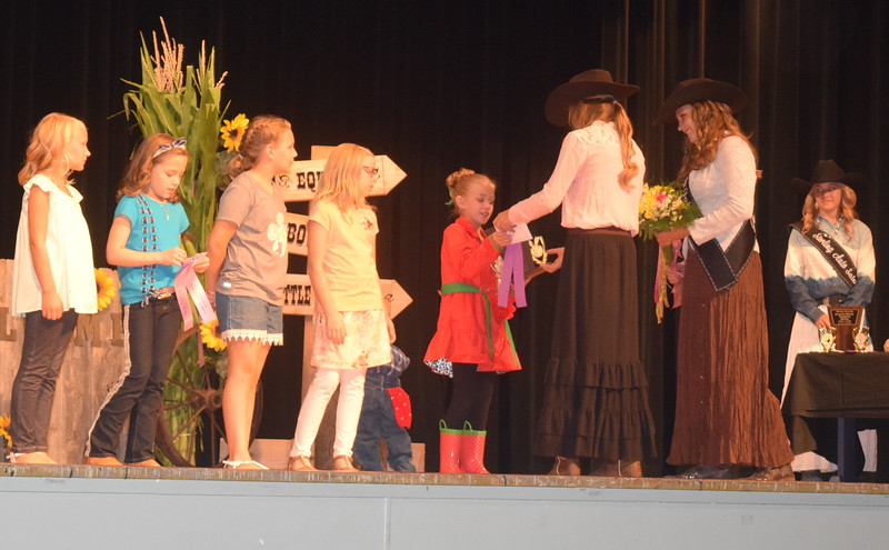 "Logan County Sweetheart Bobbie Schreiner and Queen Contestant Jessica Sigmon present awards to Hallie Lewis champion in the junior division of the ""Equines, Bovines and Little Buckaroos!"" Logan County Fair 4-H Fashion Revue Friday, July 29, 2016."