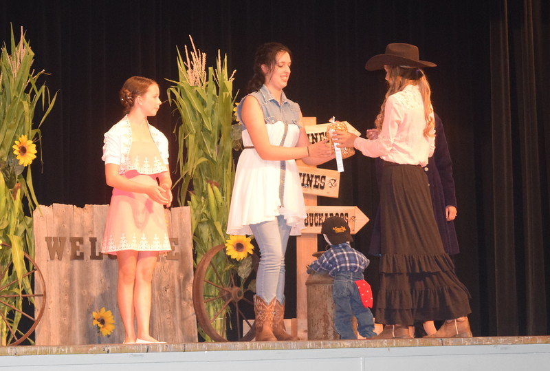 "Logan County Sweetheart Bobbie Schreiner presents a ribbon to Shelby Houser third place winner in the senior division of the ""Equines, Bovines and Little Buckaroos!"" Logan County Fair 4-H Fashion Revue Friday, July 29, 2016."