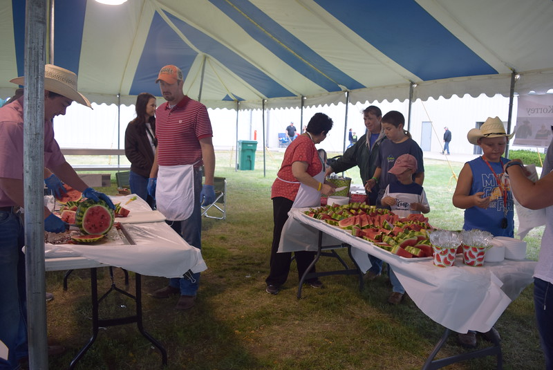 Guests line up to grab a slice of Rocky Ford Watermelon at the George and Minnie Korrey  Memorial Watermelon Feed Saturday, Aug. 6, 2016, at the Logan County Faie.