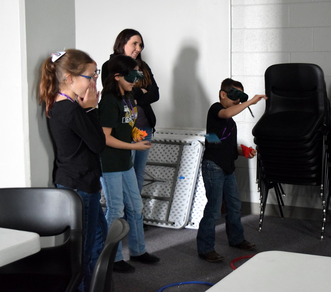 Area elementary students do a bean bag toss game wearing goggles to explore memory during one of the workshops at Brain Awareness Day presnted by Intermountain Neuroimaging Consortium Friday, Feb. 8, 2019.
