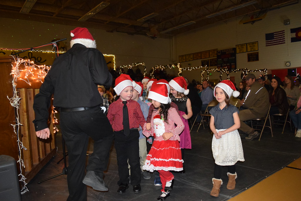 . Caliche Elementary students, all wearing Santa hats, parade out underneath Christmas arches, while the school band plays, at the conclusion of the school\'s Christmas Celebration Tuesday, Dec. 5, 2017.